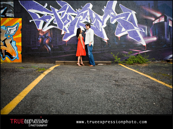 engagement photos in front of colorful graffiti wall