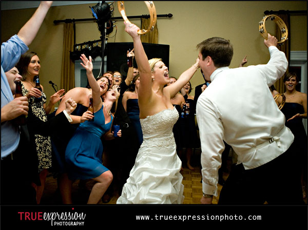 photograph of bride and groom dancing with friends