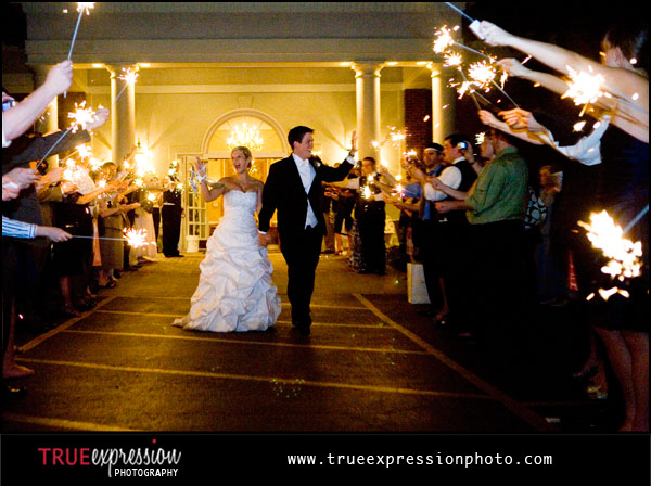 bride and groom leaving Brookstone Country Club as guests hold sparklers