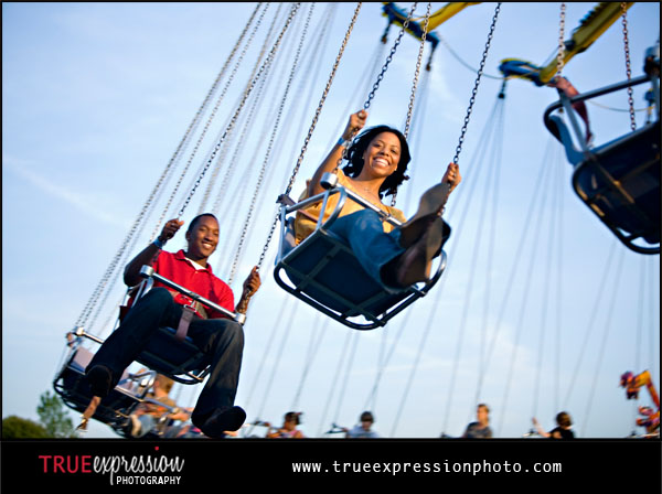 photo of couple riding swing ride at the fair