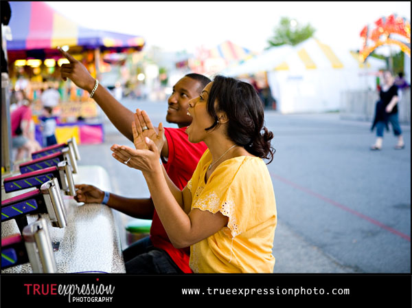 girl wins prizes playing carnival game; couple laughing