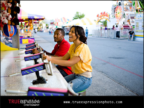 engagement photo of couple playing games at a carnival