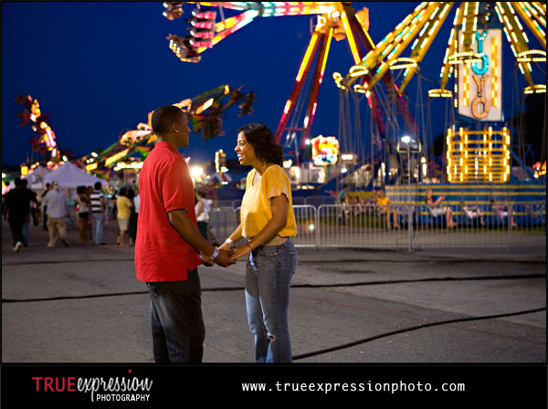 engaged couple laughing together at a carnival lit up a night