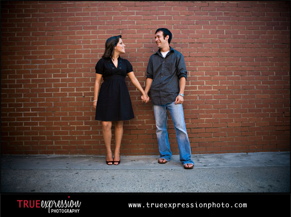 engagement photograph taken in front of a brick wall