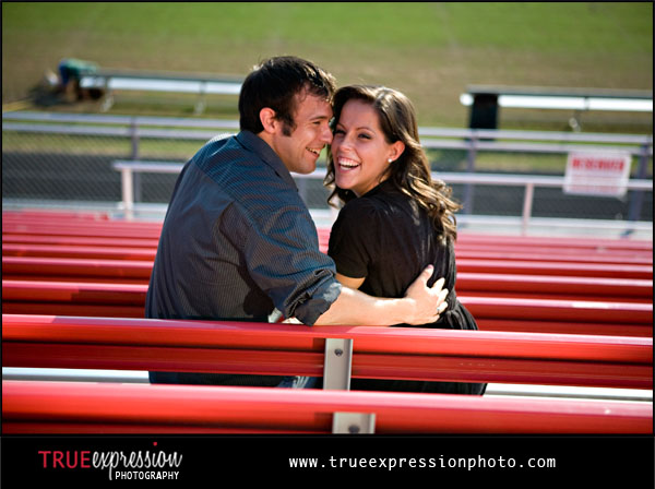 couple laughing together on red bleachers