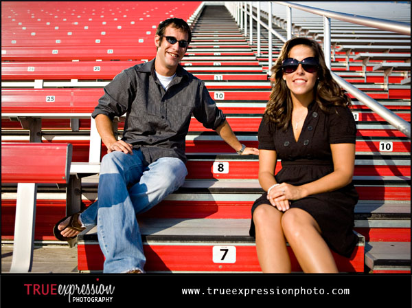 engagement photo of couple sitting on red bleachers at their high school football field