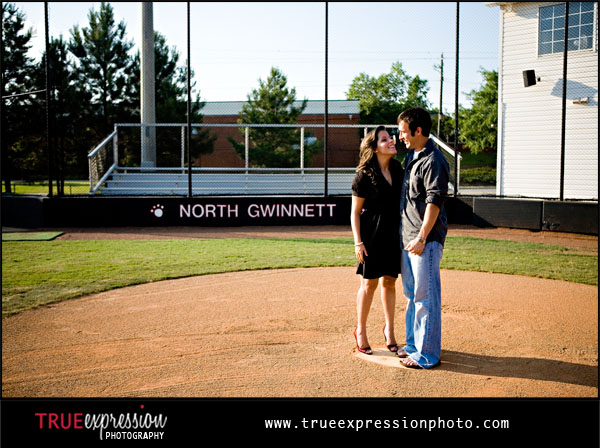 engagement photo on the softball field North Gwinnett High School in Suwanee, GA